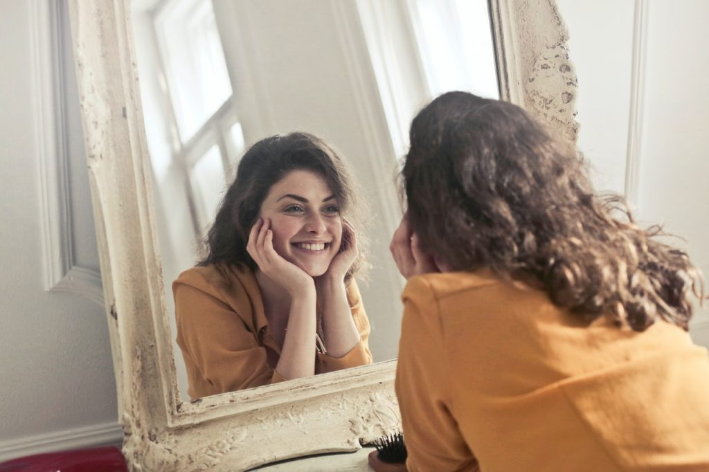 person smiling in front of mirror